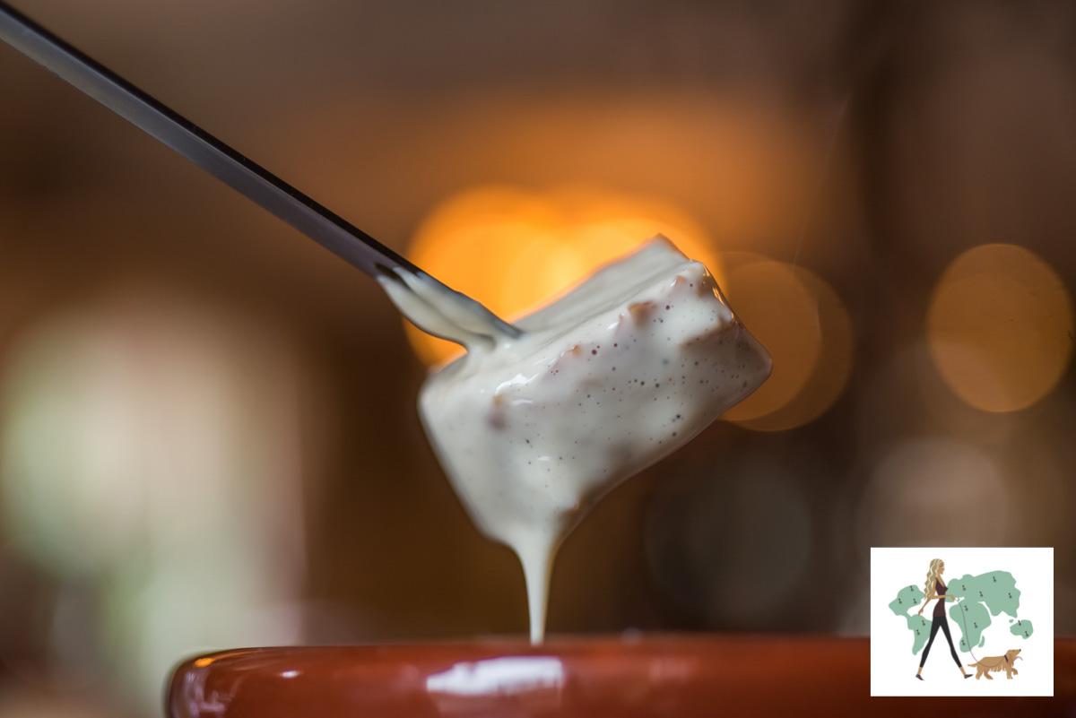 garfo espetado em pão molhado com fondue de queijo