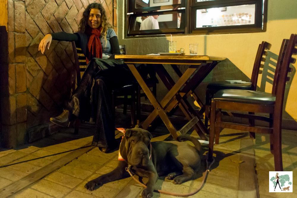mulher sentada em mesa de restaurante e cachorro no chão