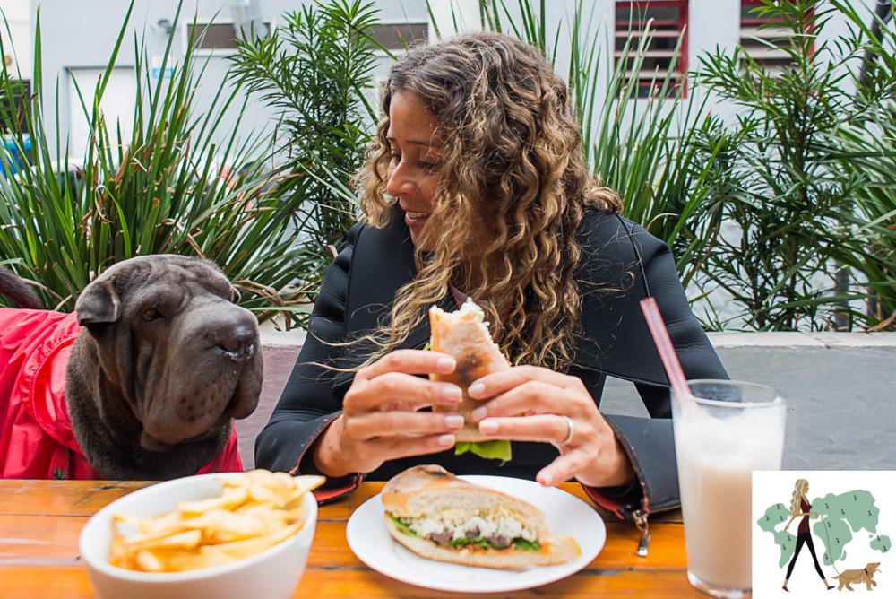 mulher comendo hambúrgue ao lado de cachorro