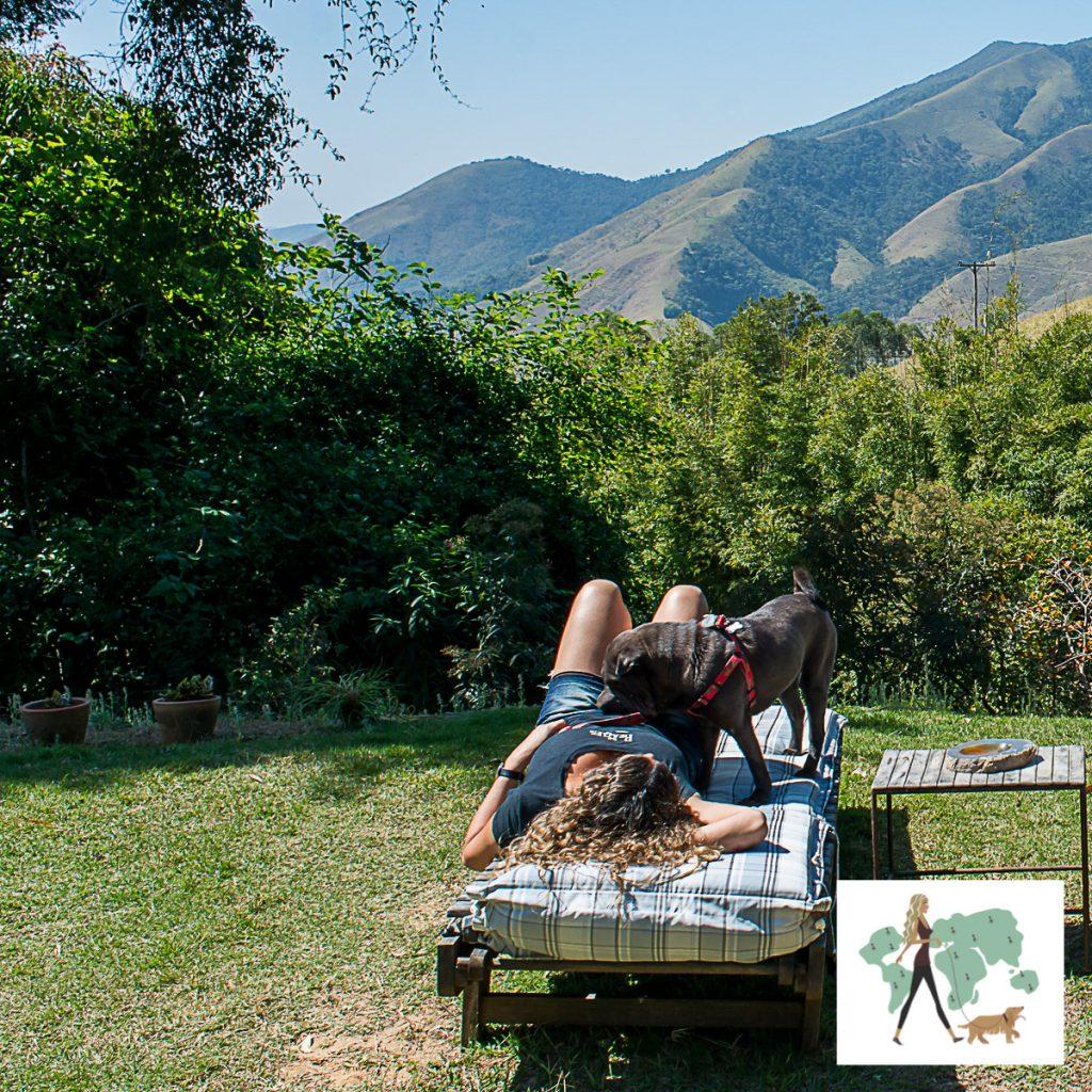 mulher e cachorro deitados em espreguiçadeira com montanha ao fundo