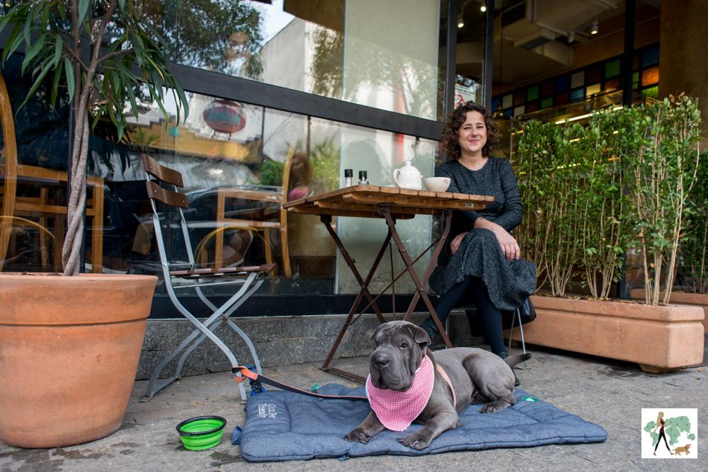cachorro deitado e mulher sentada em mesa de padaria