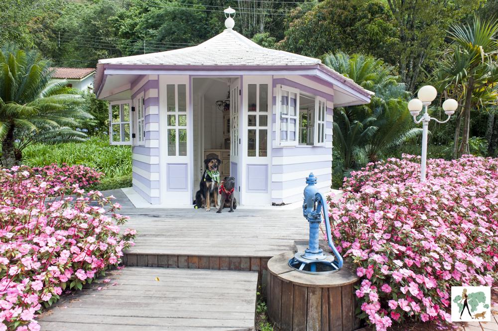 cachorros sentados em casinha com jardim de flores