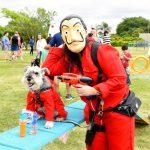 pessoa fantasiada com cachorro ao lado no parque
