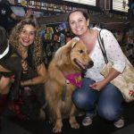 mulheres sorrindo ao lado de cachorros