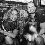 homem e mulher ao lado de cachorros