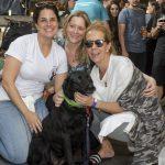mulheres sorrindo ao lado de cachorro