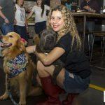 mulher de joelhos abraçando cachorros