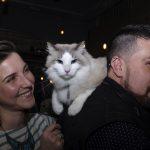 mulher sorrindo ao lado do homem com um gato no ombro