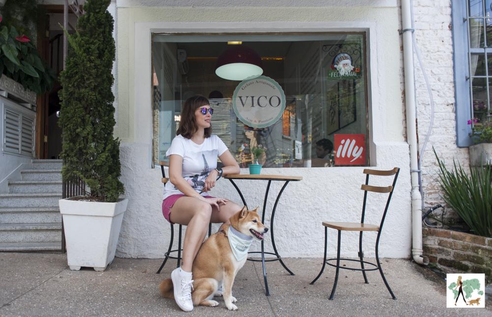 mulher e cachorro sentados na frente da sorveteria