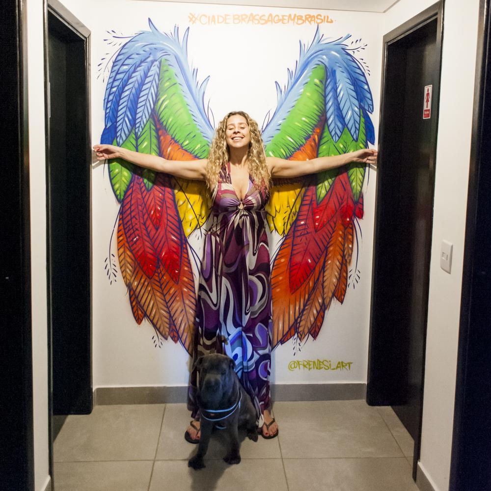 mulher de braços abertos na frente de grafite de asas
