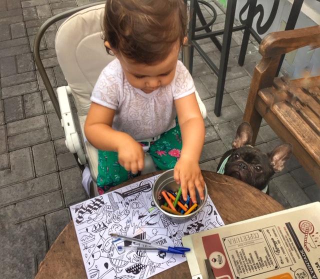 criança na cadeirinha desenhando e cachorro sentado ao lado