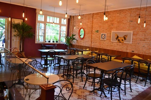 salão de um café com mesas e cadeiras