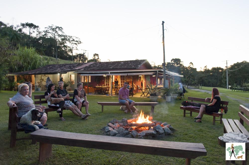 pessoas sentadas ao redor de fogueira na pousada Gaia Viva