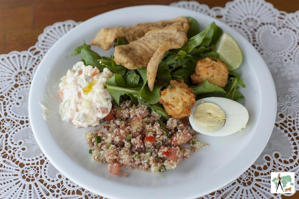 prato de tabule, salada de maionese. peixe, salada de rúcula, bolinho e ovo
