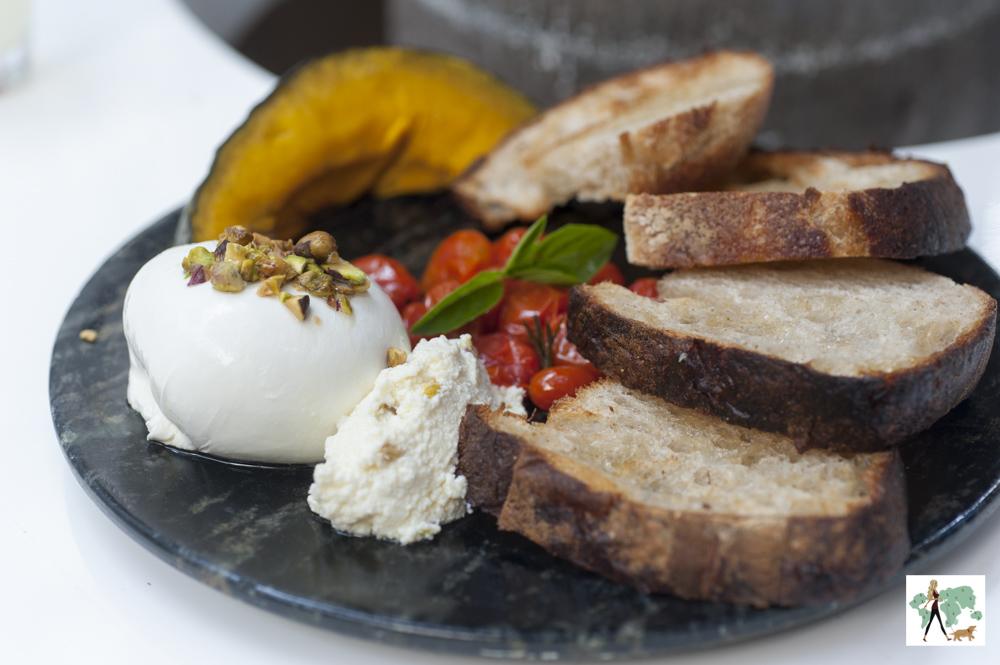 burrata com creme de ricota, tomatinho, abóbora e pães