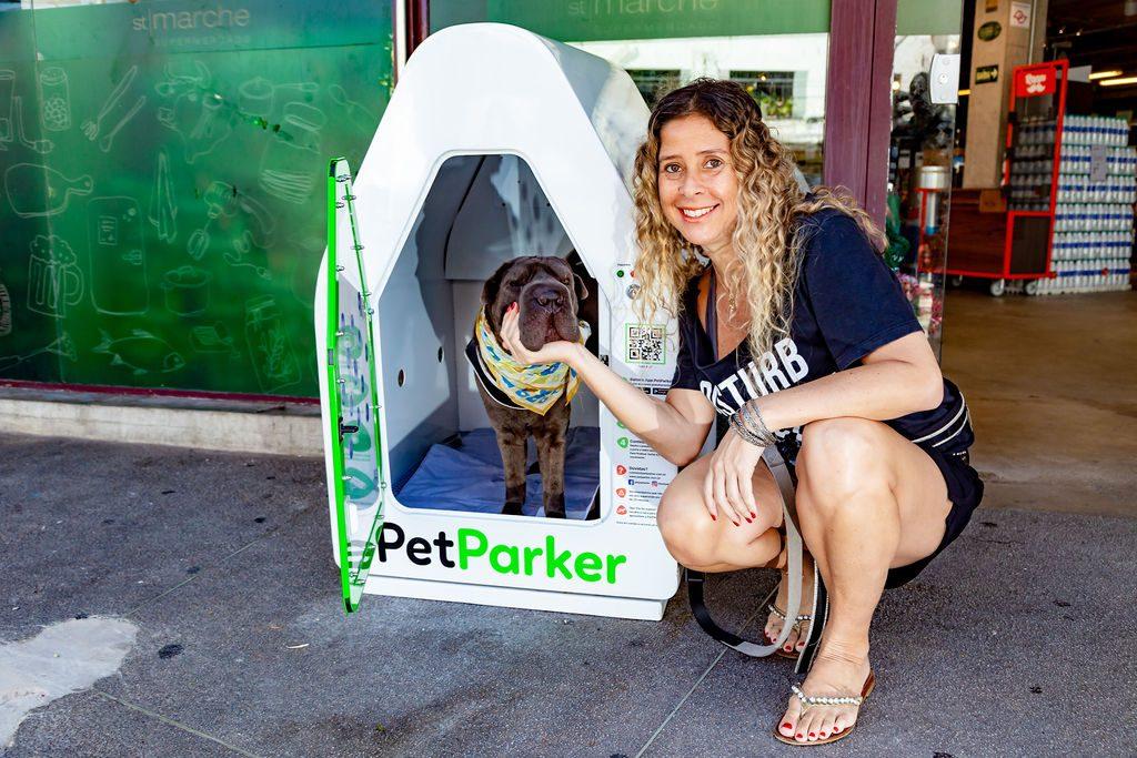 cachorro dentro de uma casinha Pet Parker e mulher ao lado