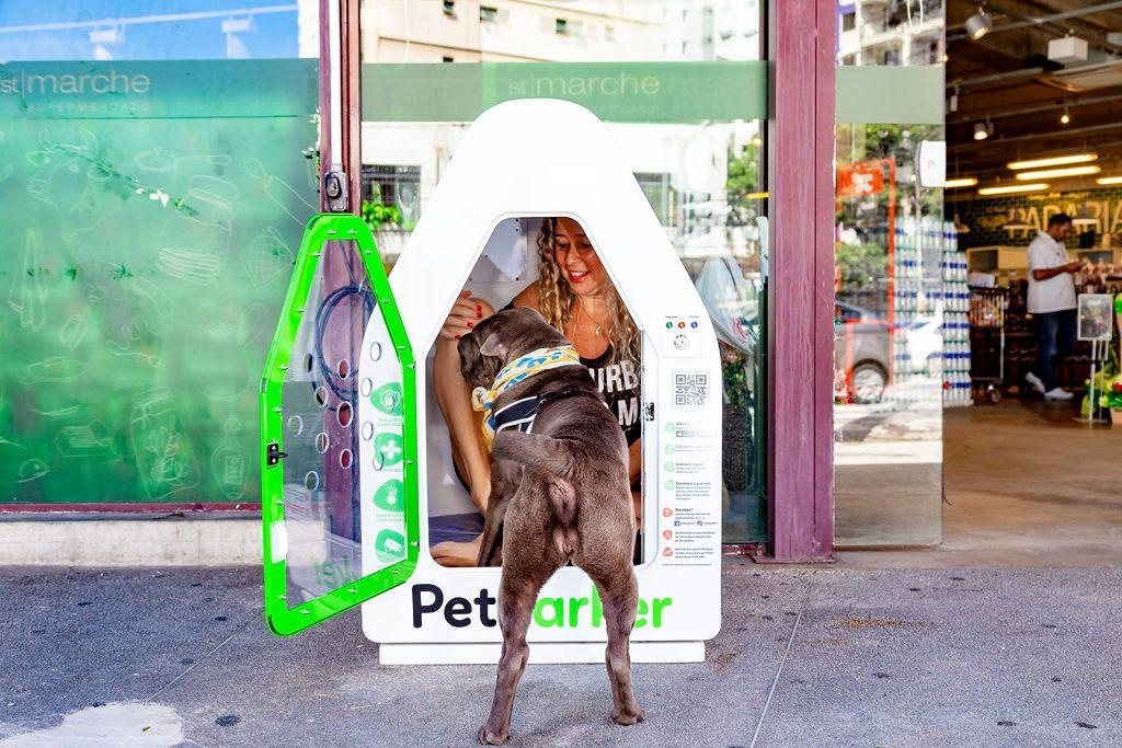 cachorro entrando dentro da casinha da PetParker junto de mulher
