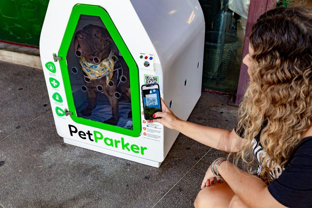 mulher fazendo leitura de QR code na casinha da petParker