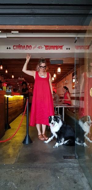 mulher de vestido vermelho e cachorro na entrada de restaurante