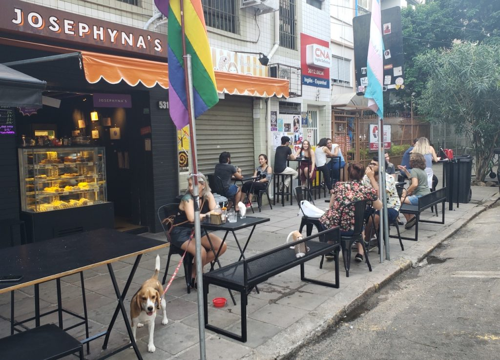 mesas em calçada com pessoas e cachorros