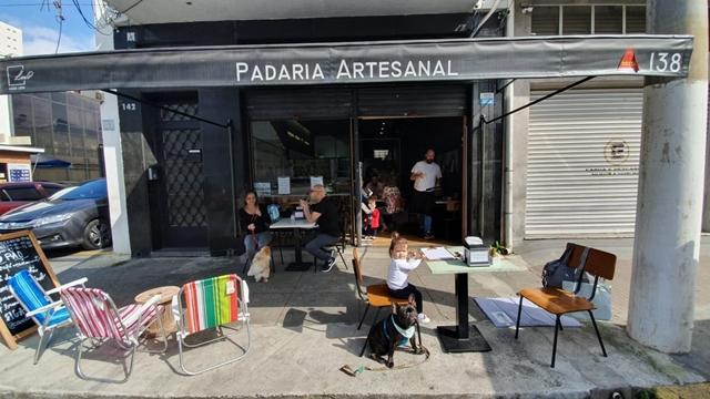 fachada da padaria com mesas na calçada