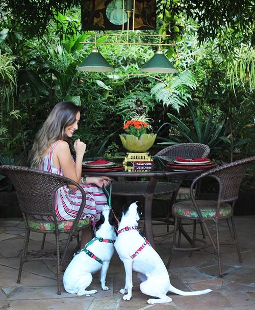 mulher sentada na cadeira com duas cachorras