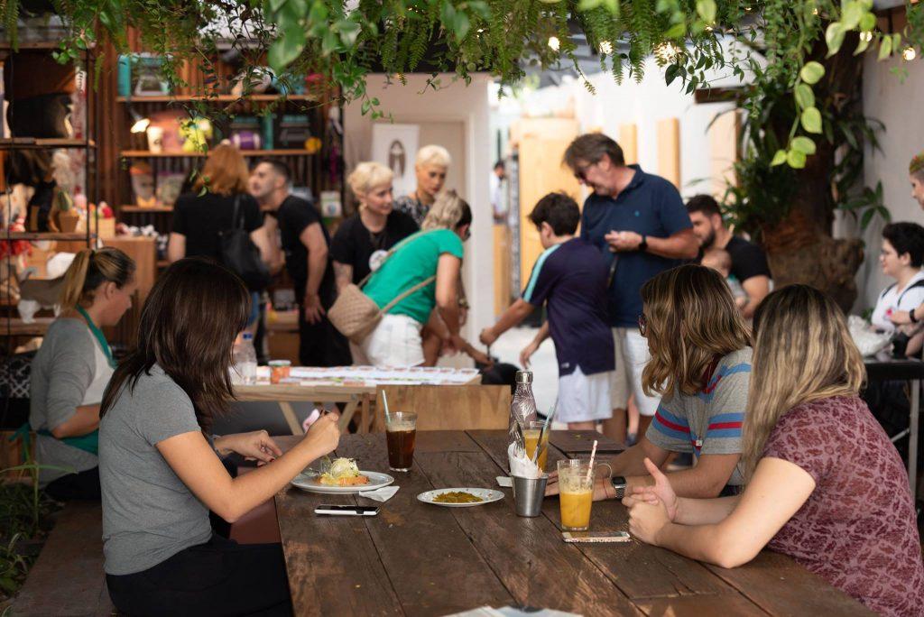 pessoas sentadas e de pé comendo