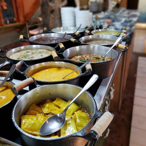 buffet com pratos quentes nas panelas