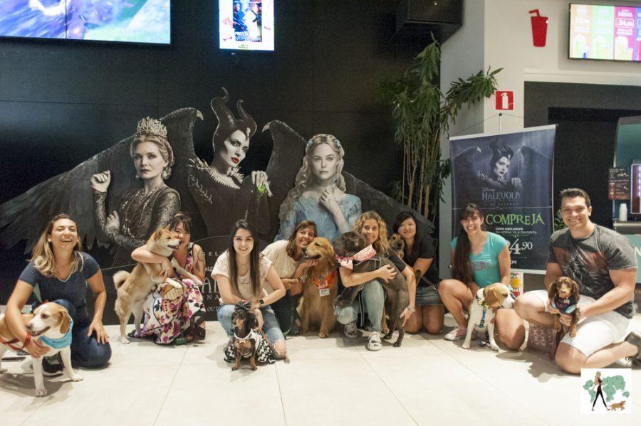 pessoas e cachorros no Cine Pets com cartaz do Malévola ao fundo