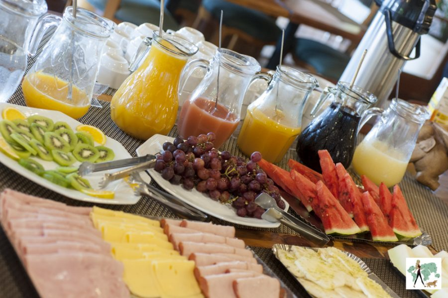 mesa de café da manhã com frutas, frios e jarras de sucos
