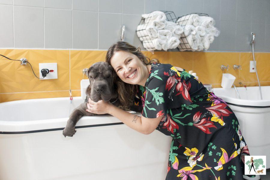 mulher abraçado em cachorro na banheira de pet shop